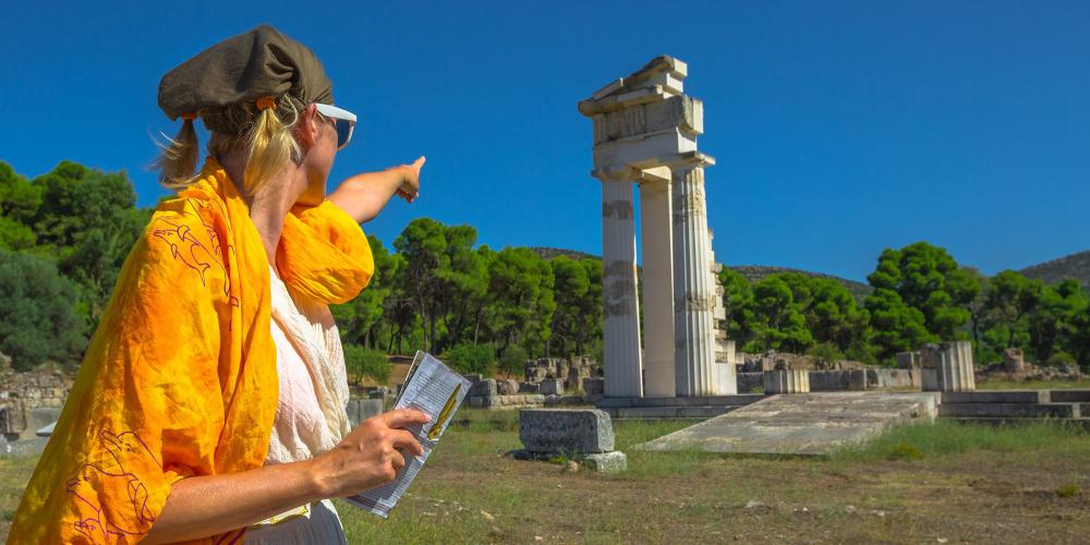 Tourist woman in Greek dress indicates the ruins of Temple of Asklepieion, Epidaurus, Peloponnese, Greece. The Sanctuary of Asclepius is a famous heritage site. – © Benny Marty / Shutterstock