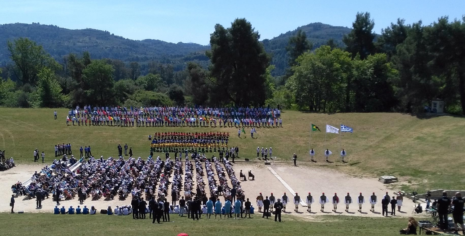 Officials and representatives of the Hellenic Republic, of the Olympic Movement and the local authorities attend the ceremony in the Stadium of Olympia. – © Hellenic Ministry of Culture and Sports / Ephorate of Antiquities of Ilia