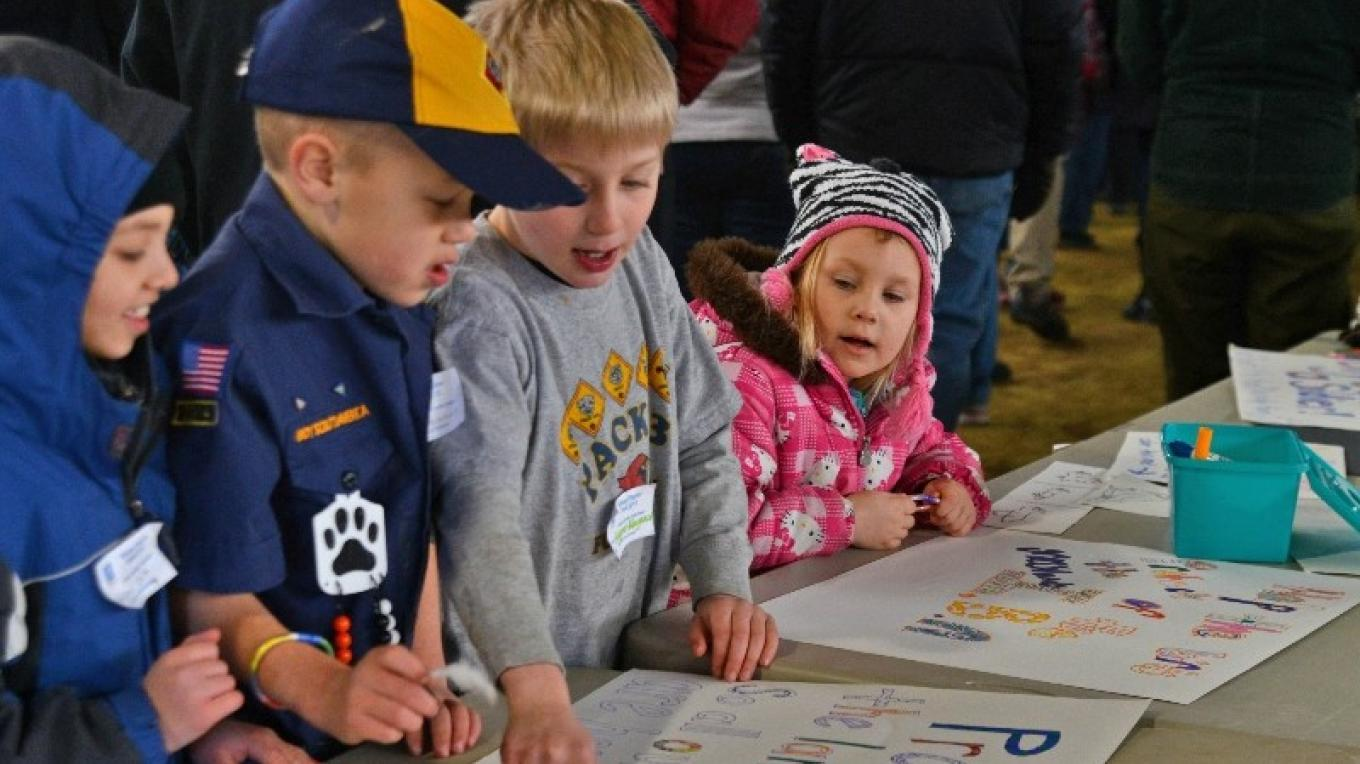 Cub Scouts help girl scouts finish posters – Connie Bush