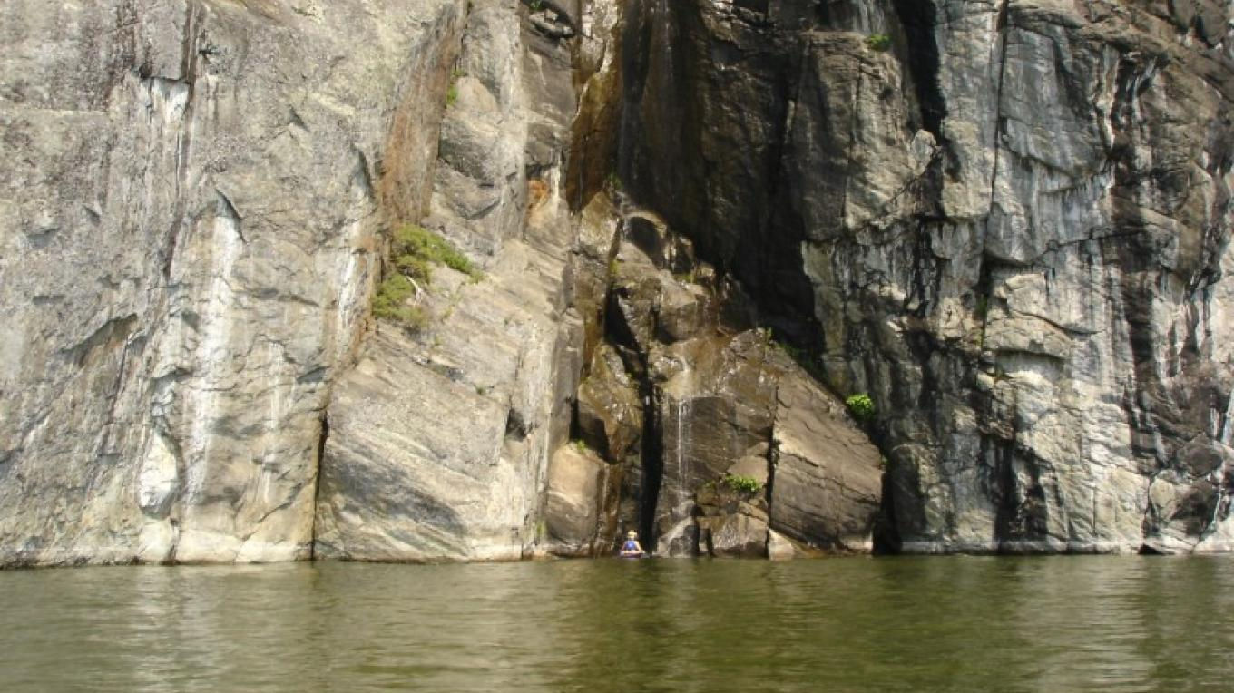 A paddler dwarfed by the waterfalls, one of the highlights of the Palisades. – Courtesy of Cathy Frank