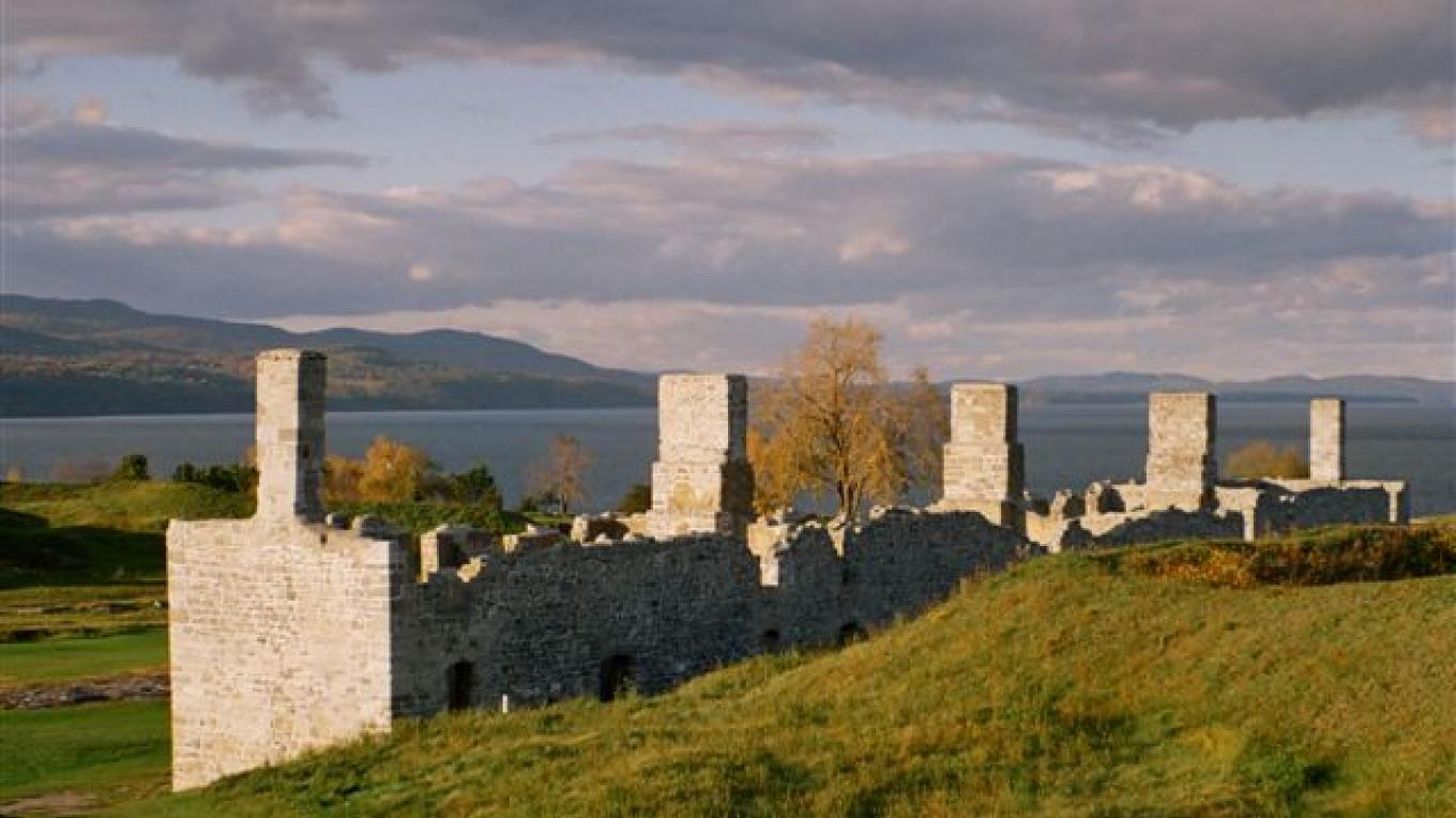 Five sunlit chimneys rise over the barracks at Crown Point State Historic Site, as the Adirondacks meet Lake Champlain in the background. – Tom Hughes
