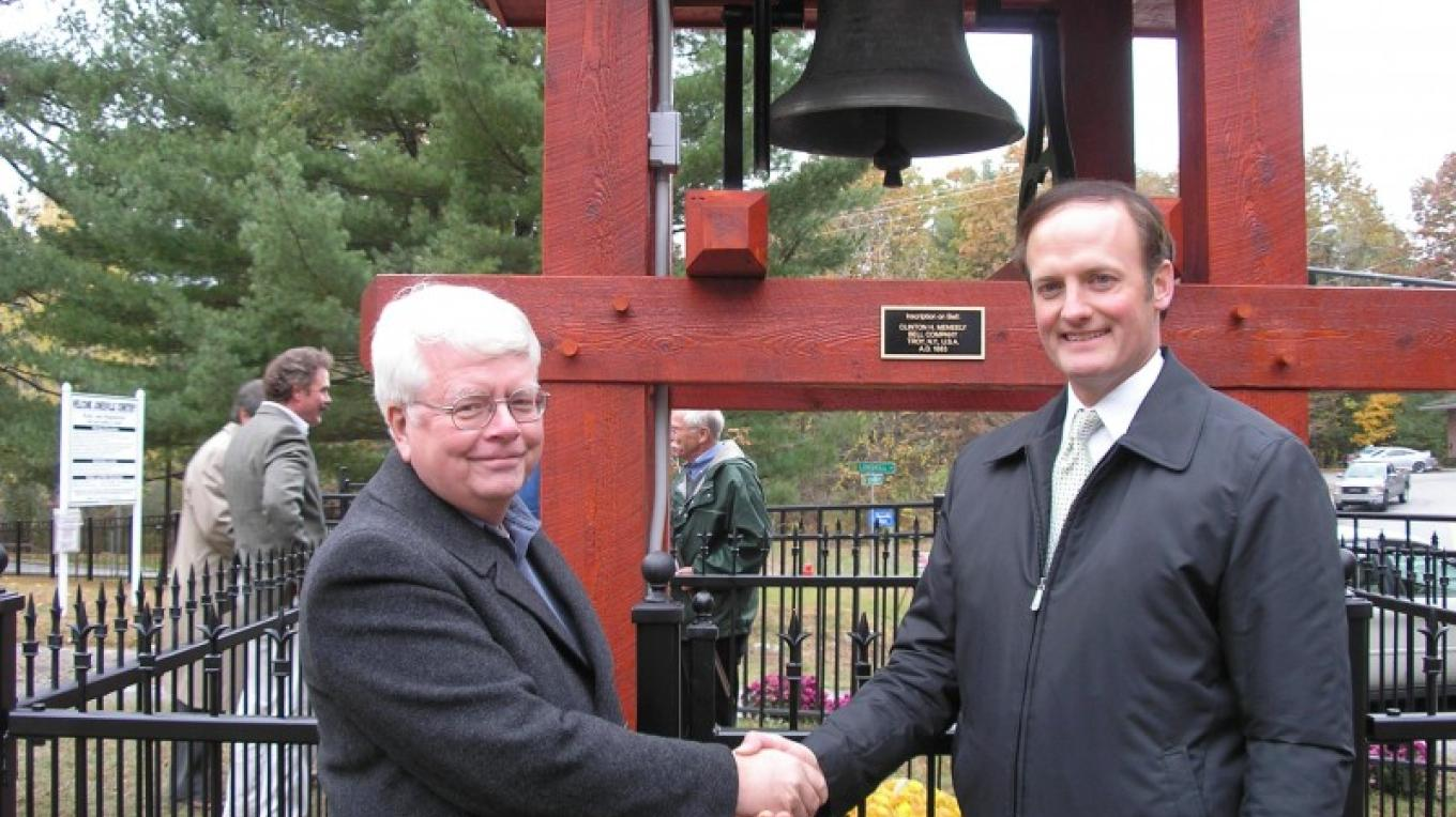 Town Supervisor Phil Barrett, right, passes over the key to the fence that surrounds the Meneely Bell in Jonesville to Jonesville Cemetery 