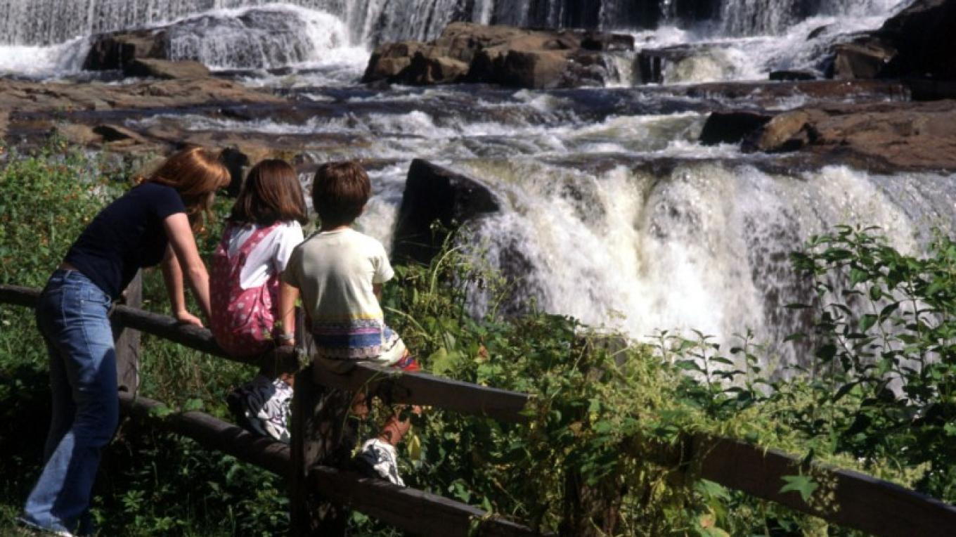 Picture of three youngsters on a fence enjoying view of the LaChute River falls along the Interpretive trail in Ticonderoga, NY. – Ticonderoga Chamber of Commerce