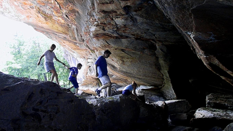 Family friends exploring under the Natural Stone Bridge cave entrance. – Greg Beckler