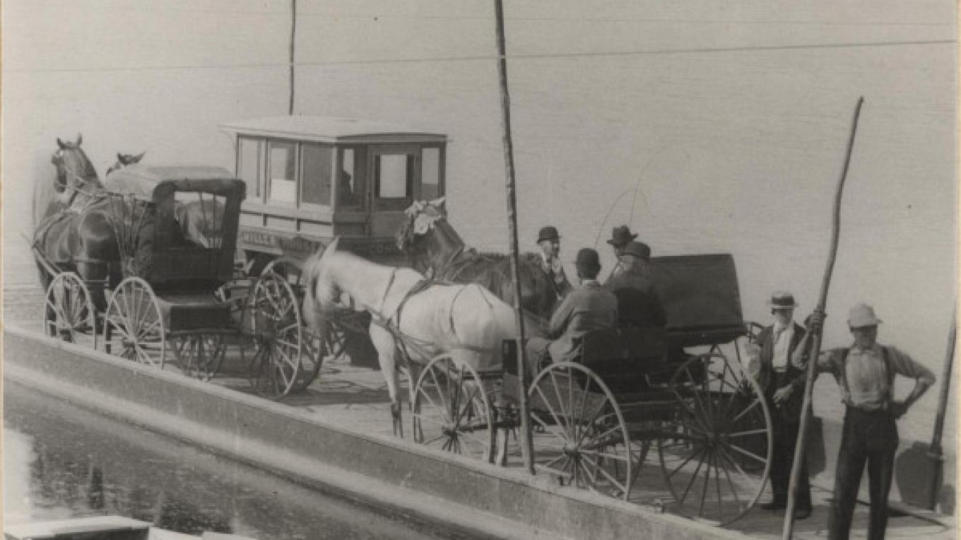This picture is dated approximately 1895. A ferry crossing the Mohawk River at Dunsbach Ferry The tall poles on the ferry helped to kep the cables from swinging over the horses heads. – Town of Clifton Park History Collection