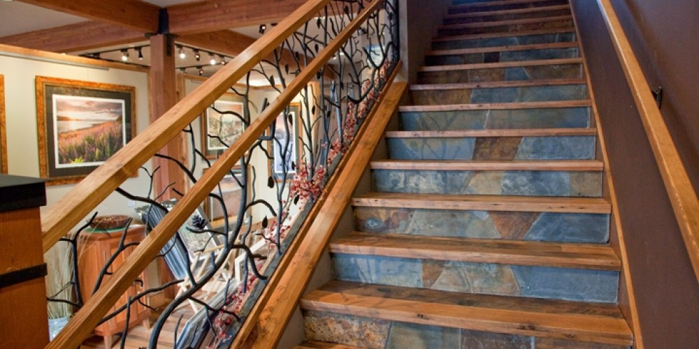 Reclaimed barnwood and slate stairs to the upstairs gallery are complemented by ornamental wrought iron branches. – E. Carmel