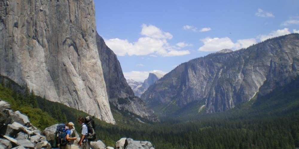 Backpackers in Yosemite Valley with El Capitan and Half Dome in the distance