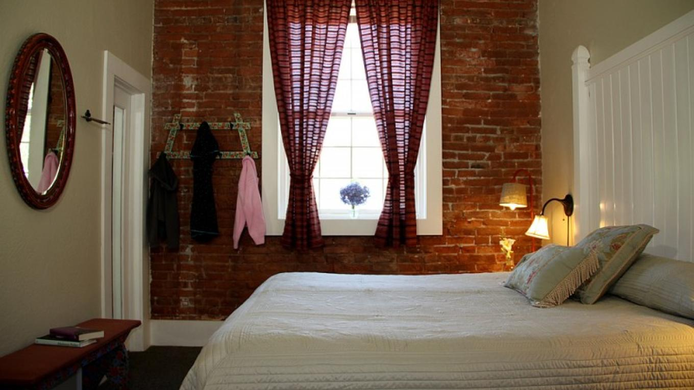 Guest room in historic hotel.  Original brick walls, large operable windows, air-conditioning, private bath, fine linens, unique furnishings, free wi-fi – Christine Gustafson