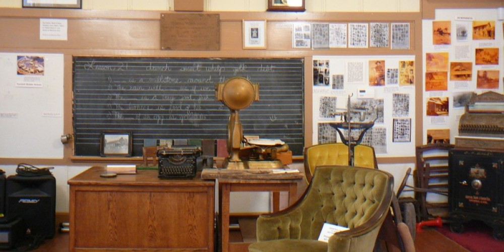 School house interior cushioned chair in front of desk from passenger car SJ&E railroad – Susan Leeper