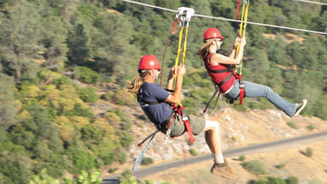 2 people race the ZIP LINES at Moaning Cavern Park high above the rolling foothills of the Sierra Nevada. – Lisa Boulton