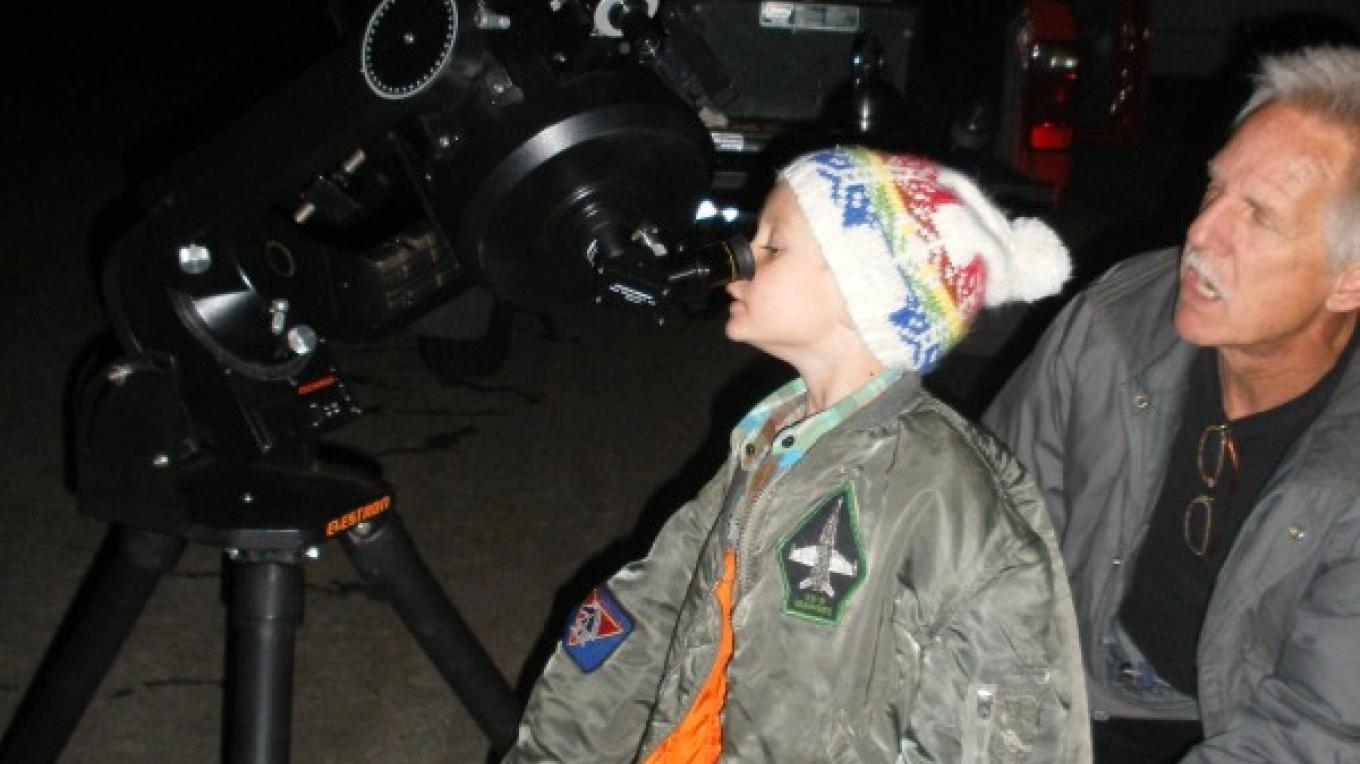 Rich shows off the Orion Nebula to a young visitor. – Dianna Anderson