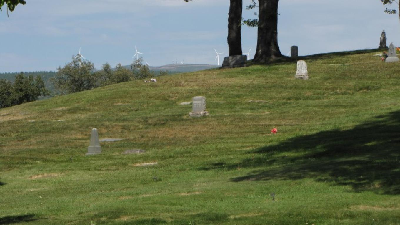 Halcumb Cemetery with the Hatchet Ridge windmills beyond. – Ben Miles