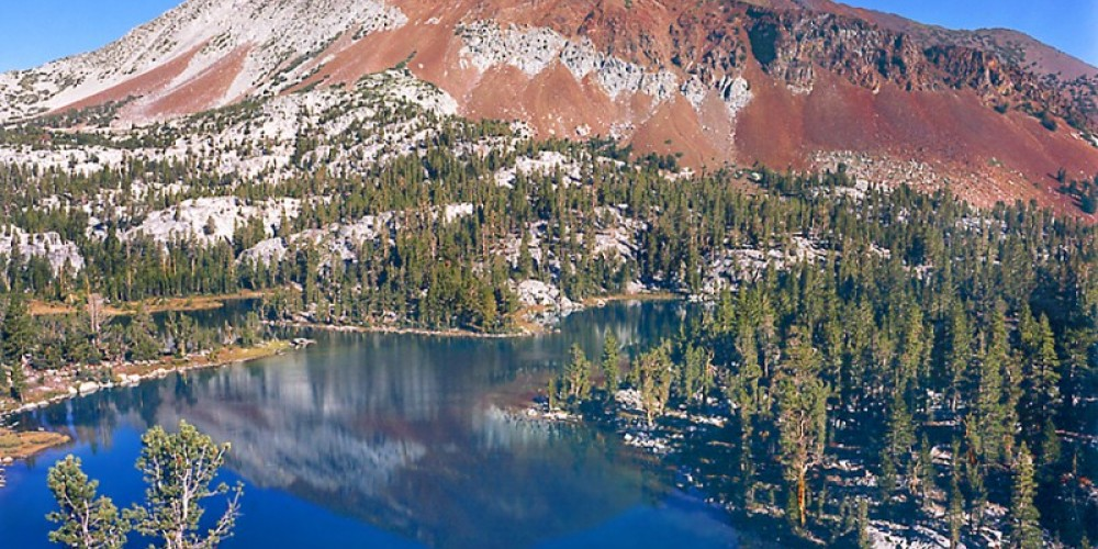 The darker, north side of Bloody Mountain, (12,544 ft) in the John Muir Wilderness Area, is easily seen and overlooked on Highway 395 just south of Mammoth. On the sunlit south side of the mountain is the Convict Creek Basin. – Fred Weyman