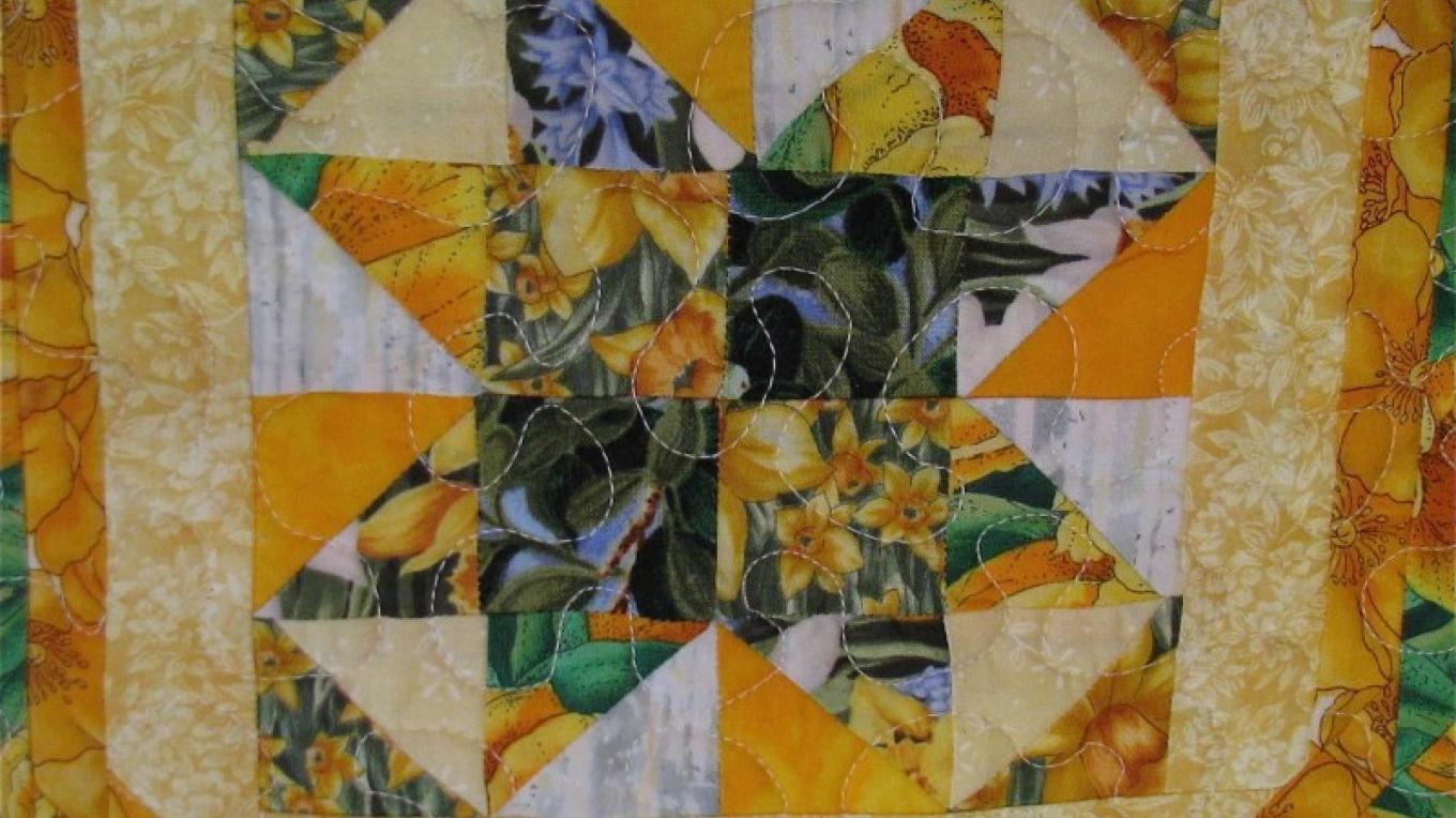 This is a close up of a square in a table runner. – Karrie Lindsay