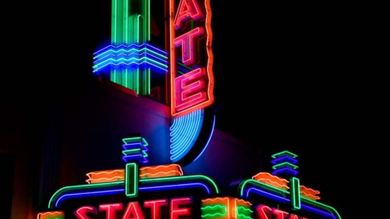 The marquee and blade sign of the State Theatre in downtown Auburn illuminates Lincoln Way, the historic street, and once highway, winding from Old Town Auburn through downtown Auburn. – Tony Perterson AJPN Photo