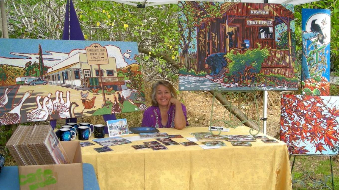 Artist Nadi Spencer at her colorful booth with lots of Kaweah Post Office artwork – CJS