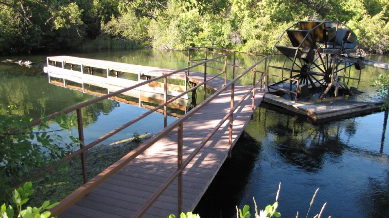 Dock and waterwheel in Fall River at the Spinner Fall Lodge. – Ben Miles