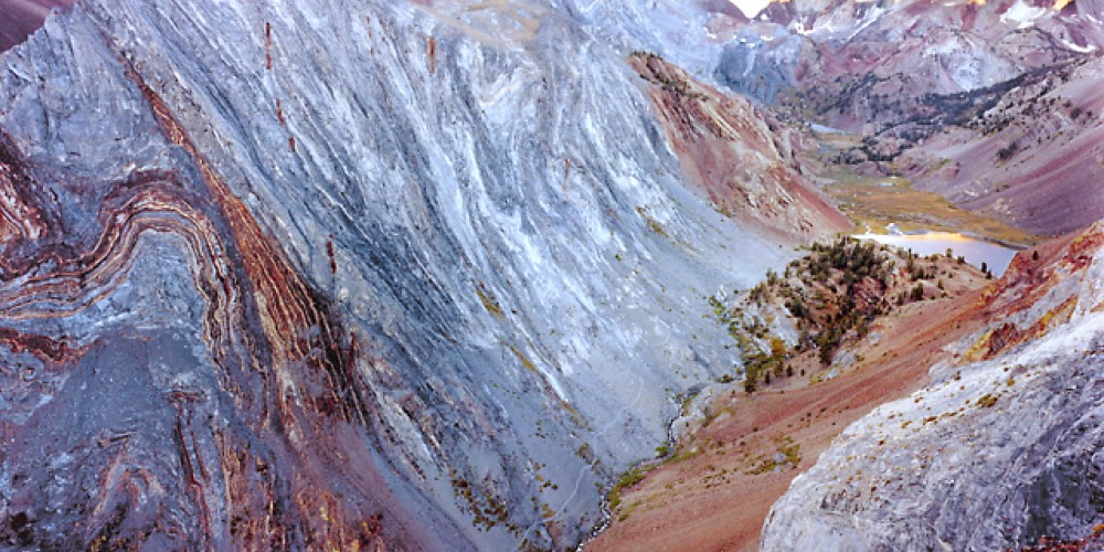 This twisted marble 'signature' of the Convict Creek Basin masterpiece is on a thin ridge separate from the main ridge connecting Mt Morrison to Mt Baldwin (center, 12,600 ft.). The final mile of the trail up the canyon. – Fred Weyman