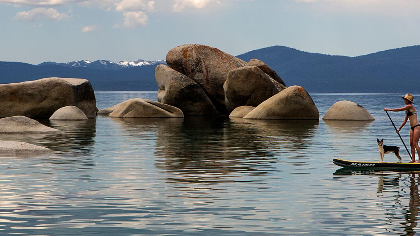 A standup paddleboarder enjoying calm waters and scenery on Lake Tahoe. – Photo by Ryan Salm