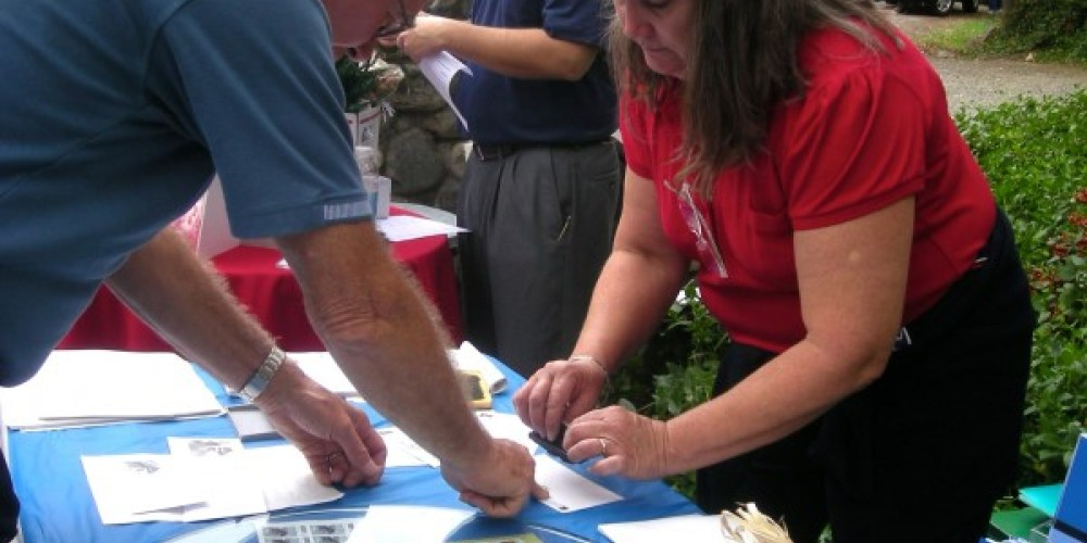Postmaster Lori Ontiveros using the special 100 year cancellation stamp for a collector – CJS