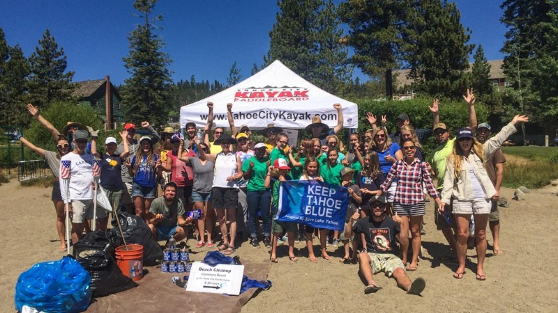 Community members celebrate at the close of a beach cleanup – League staff