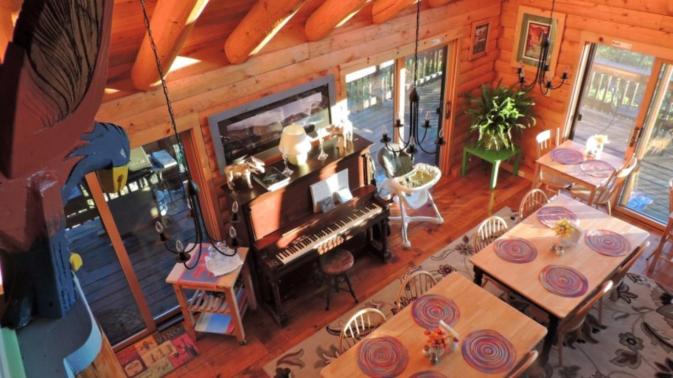 The Dining area has an open floor plan adjacent to the Kitchen and Great Room. It shares the wall of floor-to-ceiling windows featuring the incredible views at Lillaskog Lodge. There is plenty of room for a larger group to gather for meals. The wraparound deck has tables for extra seating or enjoying a meal or beverage while watching our stunning sunsets. A piano is available in the Dining Room for those who are musically inclined.