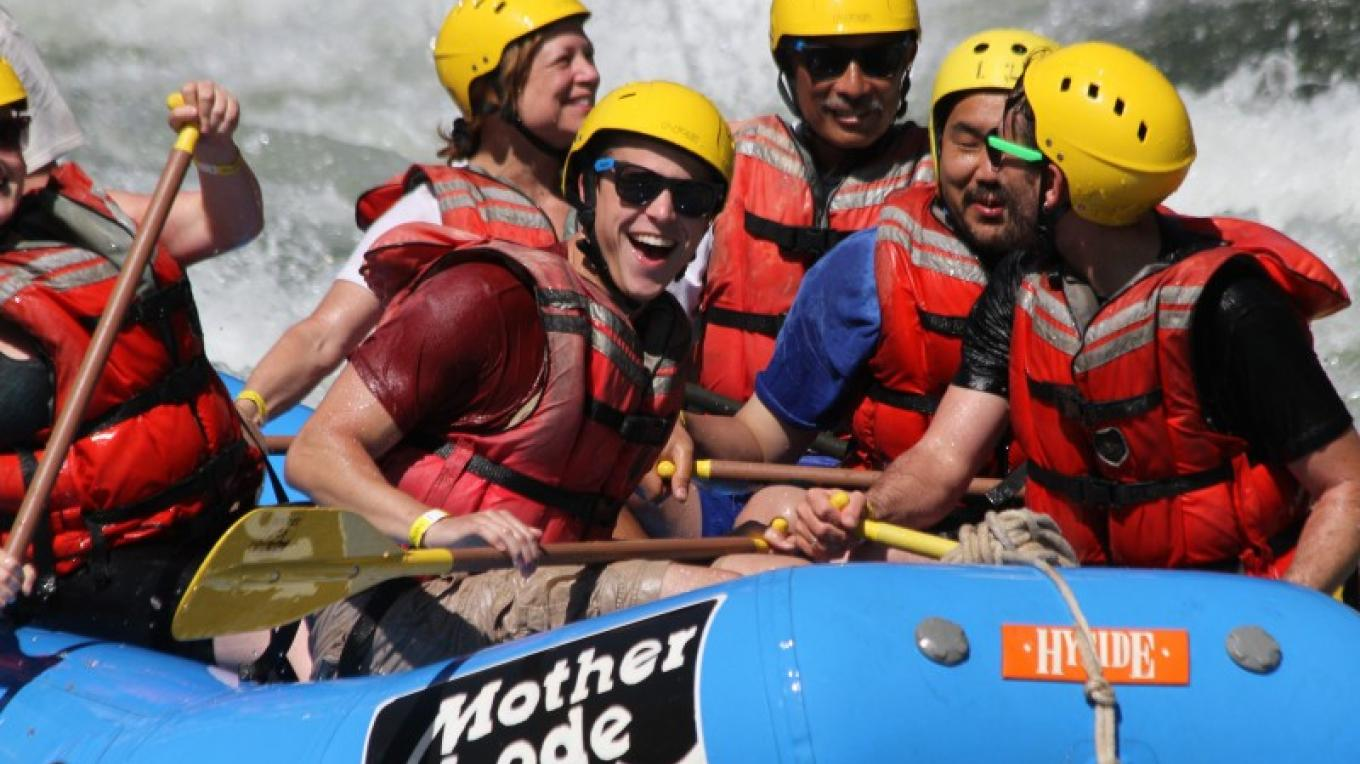 Paddlers are all smiles after successfully paddling through the Class III Satan's Cesspool rapid on the South Fork American River.