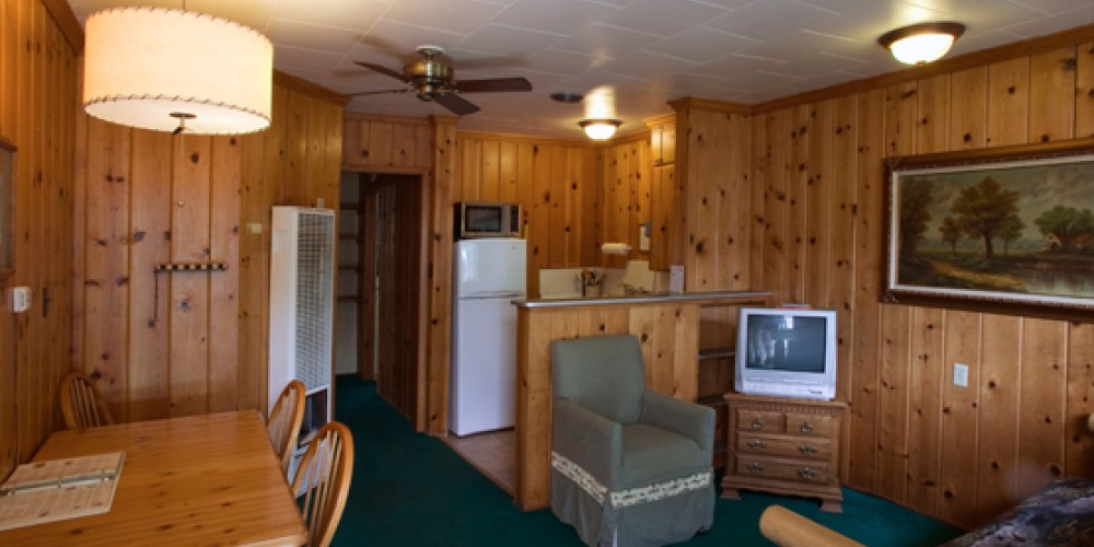 Knotty pine interiors line the living room of this cabin. – Lake Front Cabins