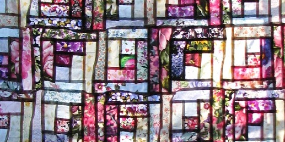 Before final quilting, the top fabric looks like stained glass! – Karrie Lindsay