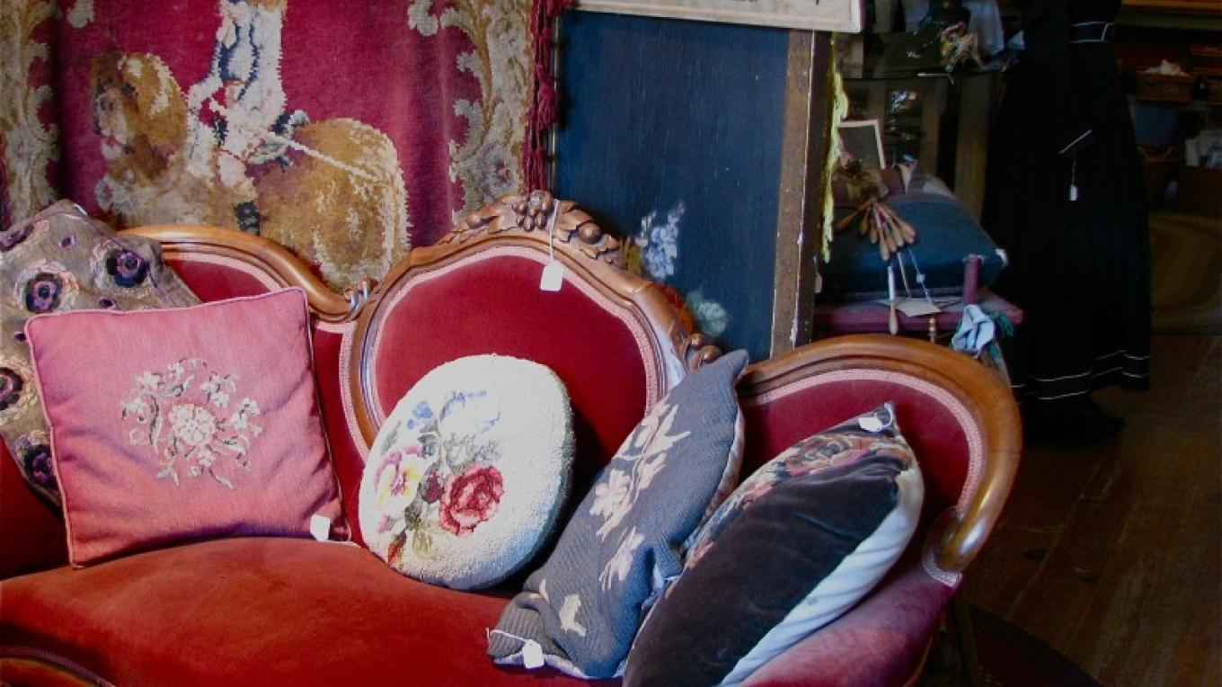 Fine furniture of the era graces the shop. At various times, antique spinning wheels, spinning chairs, bureaus, chairs, trunks plus other furniture are displayed among the personal adornment items. – Karrie Lindsay
