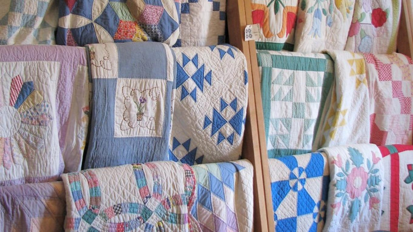 Antique quilt collection ranging from the pre1900s to the Depression era. Sally hand picks the quilts for skill of design and sewing. – Karrie Lindsay