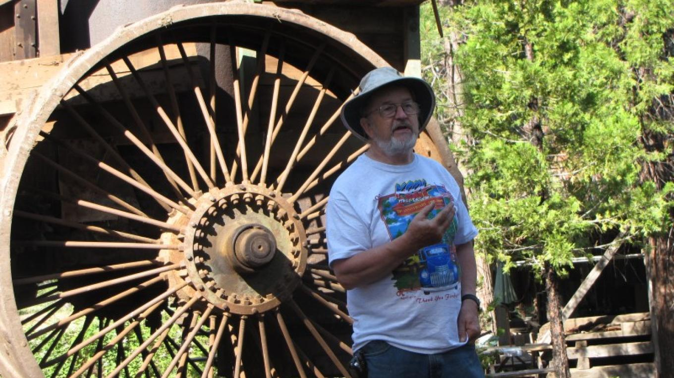 Gary Hendrix explains  his family's Phillips Brothers Mill on a tour of the property, in front of an antique steam-powered tractor. – Ben Miles