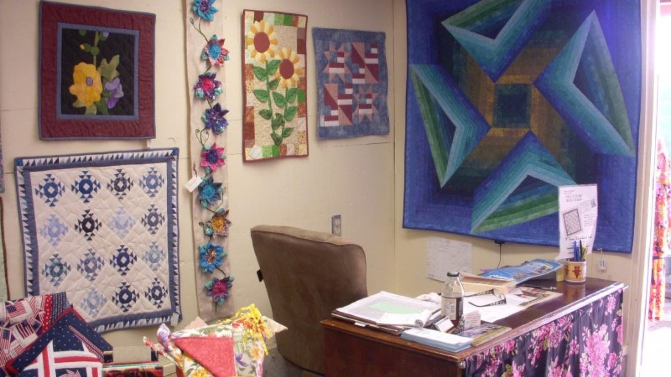 Interior of shop showing a variety of wall hangings – Pat Lawrence