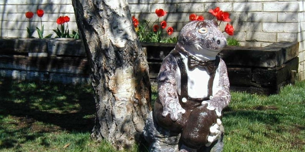 Our own Sierra Toad watches over the property and the spring tulips – Lake Front Cabins