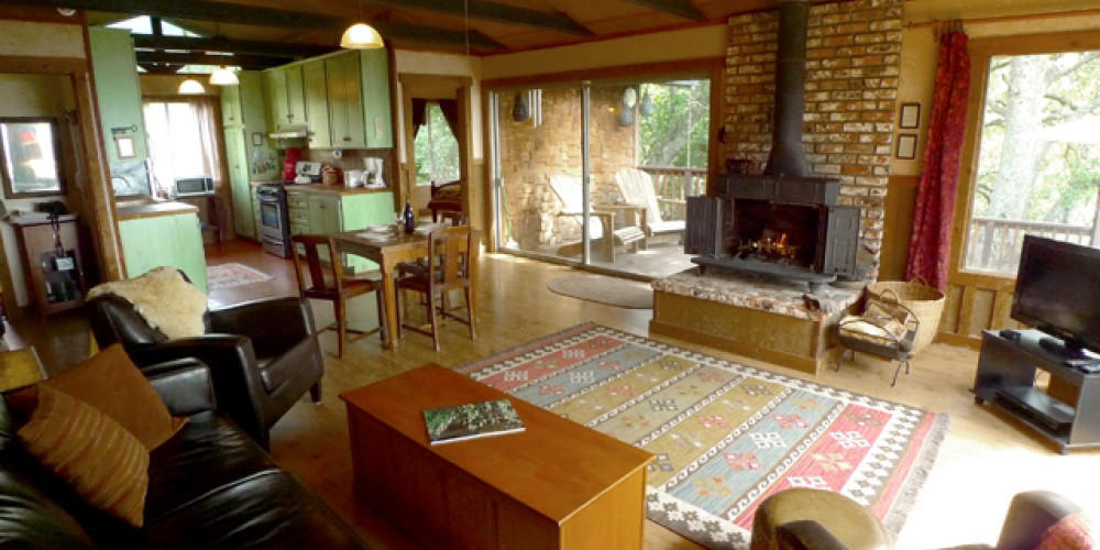 Living area with wood stove and kitchen beyond at the Waterfall cabin – Shelly McKnight