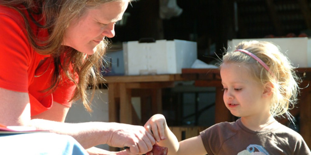 Laurie Noble samples a pluot with a young Passport Weekend visitor. – David C. Neilsen II