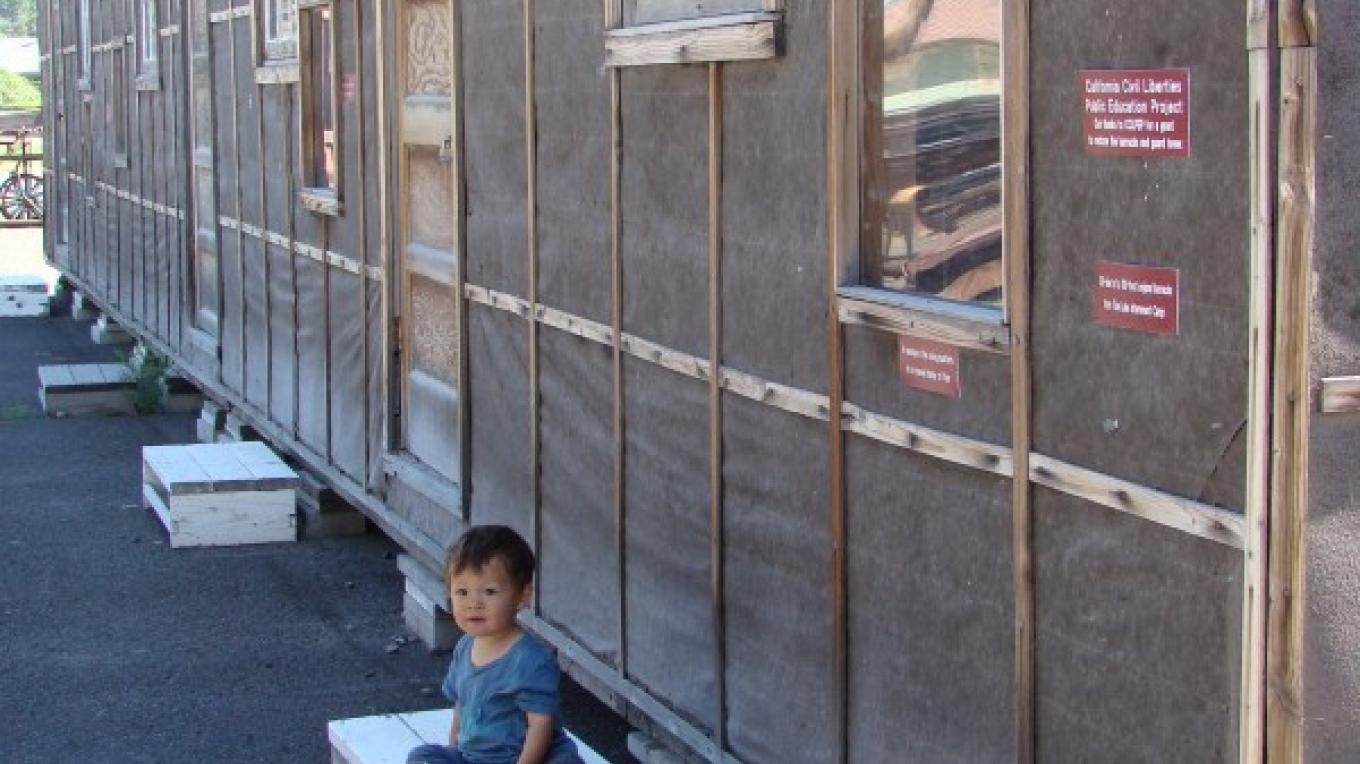Kenji Nakano Ross age 1 sits in front of a model of the Tule Lake Internment Camp barracks where his great grand-uncle and other relatives were housed. – Jean Bilodeaux