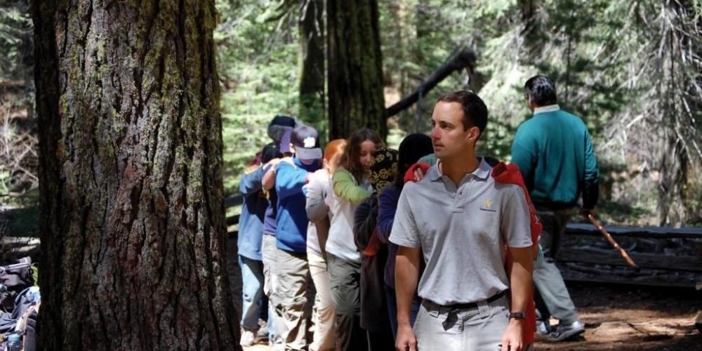 "NatureBridge field science educator, Bryan Batdorf, leads students on a ""blind"" sensory walk in Yosemite Valley."