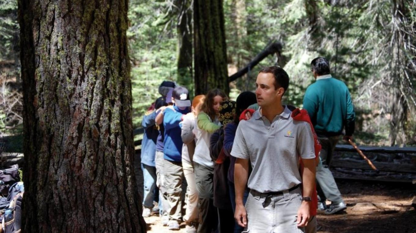"NatureBridge field science educator, Bryan Batdorf, leads students on a ""blind"" sensory walk in Yosemite Valley."
