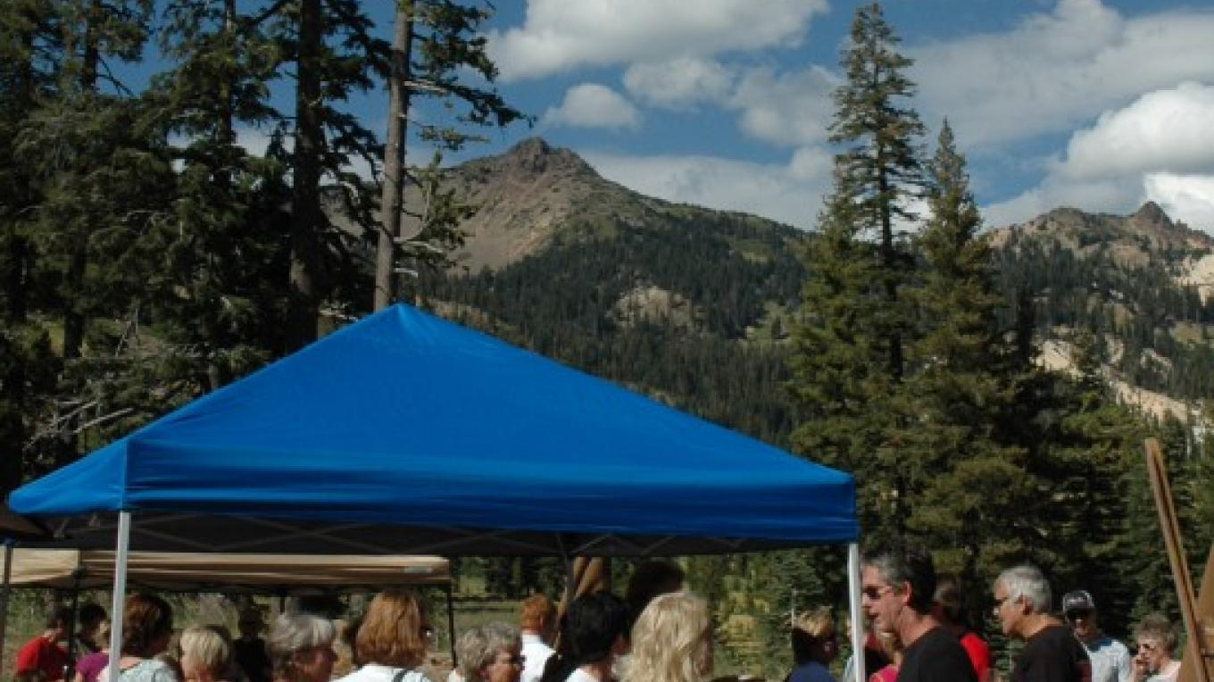 Mt. Diller and Pilot Pinnacle tower behind guests enjoying wine tasting and hors d'oeurves – NPS Photo