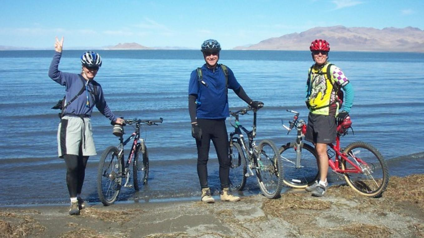 Riders dip their front wheel at the Tahoe Pyramid Trail's terminus, Pyramid Lake.