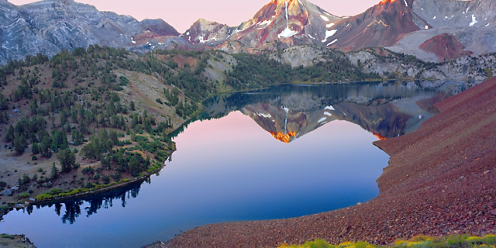 On my first visit to Convict Creek Basin a constant strong cold wind forced me to strap rocks to the tripod at this same location. On the return trip, calm conditions allowed Lake Dorothy (10,275 ft.) to reflect the sunrise. – Fred Weyman