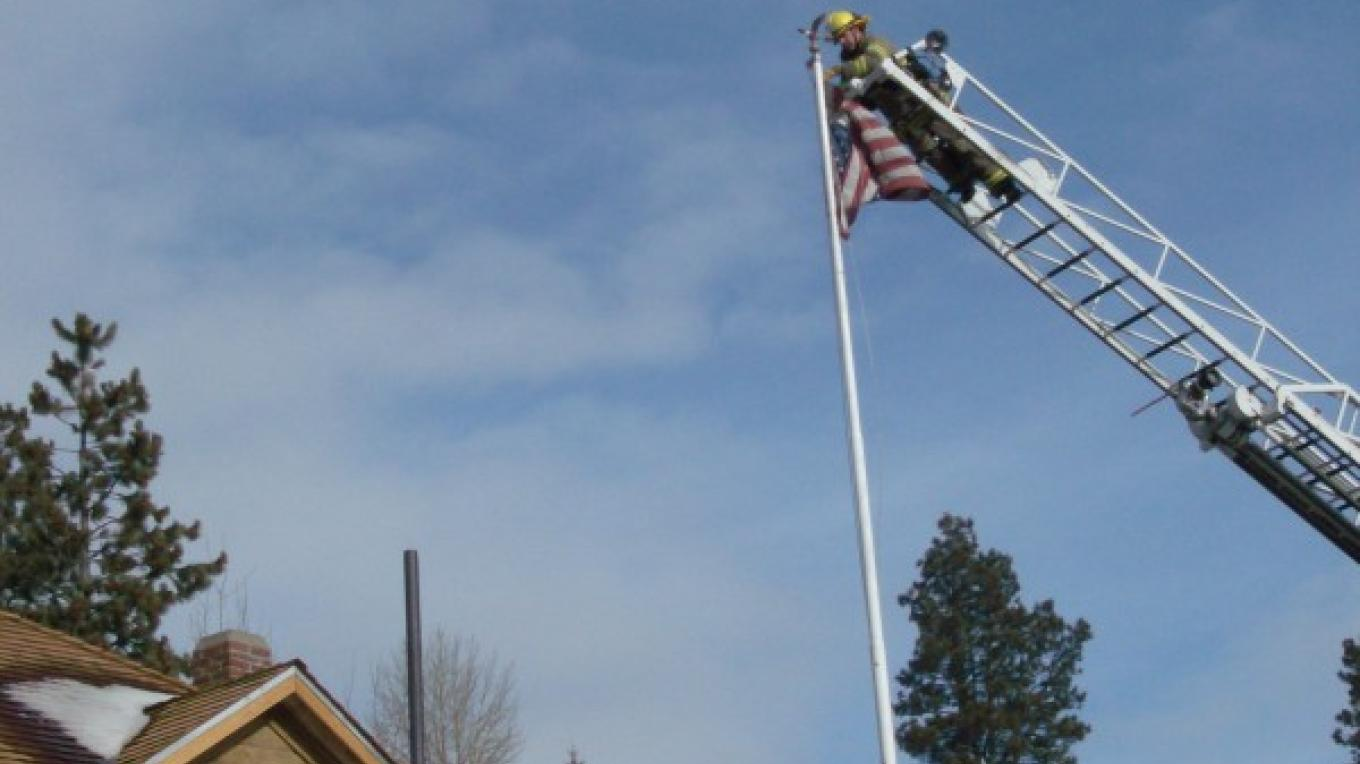 Truckee Fire to the rescue.  Removing torn flag at the Old Jail March 2010. – © 2010 Truckee Donner Historical Society All Rights Reserved