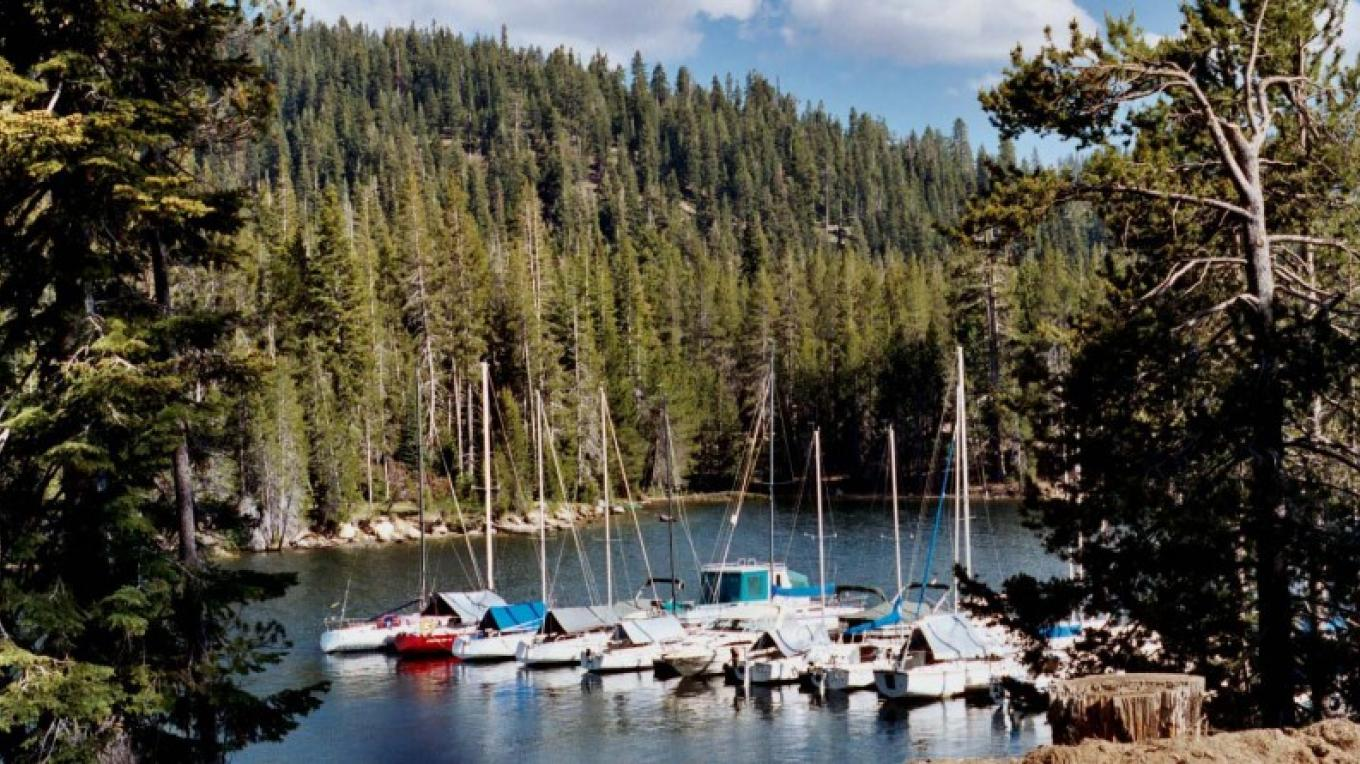 A lightly clouded blue sky peaks over the heavily forested banks of Huntington Lake. – Sue Exline, USDA FS