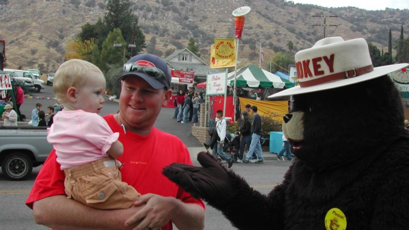 Everyone gets in on the festivities - Smokey Bear greets one of the smallest. – Marilyn Knesel