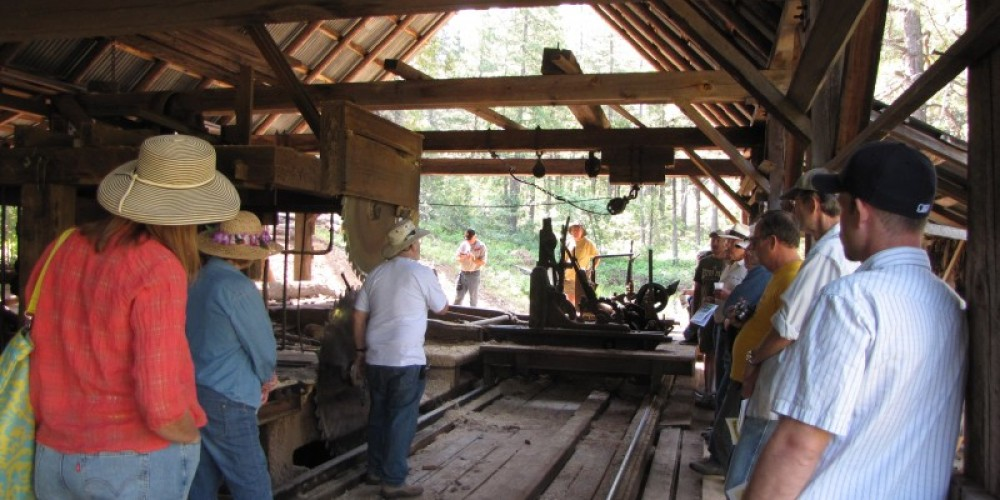 Attendees listen as the inner workings of the steam-powered mill are explained during a tour. – Ben Miles