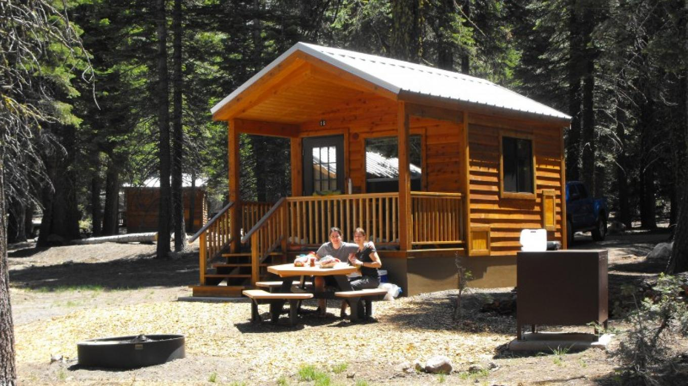 Campers enjoy a picnic infront of a camping cabin. – Greg Brahms