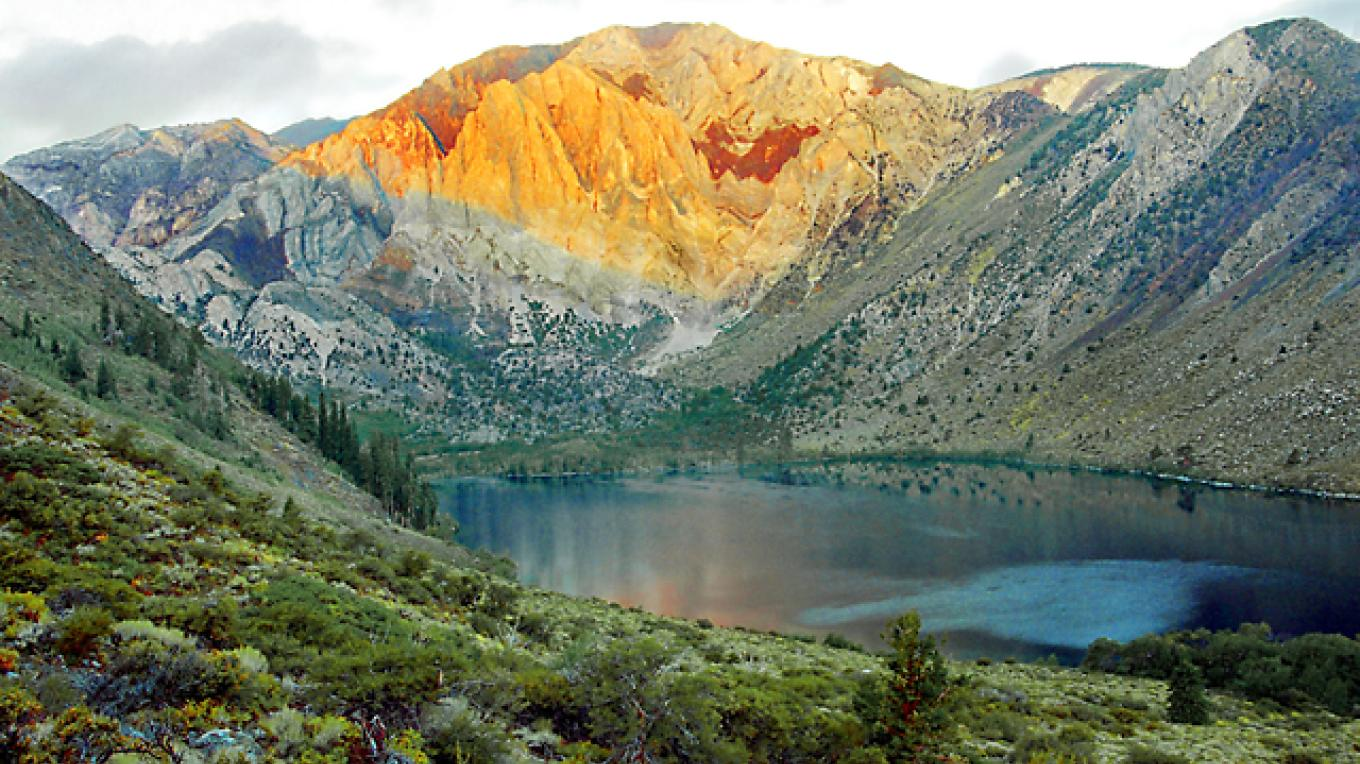The early sun hits the Sevehah Cliffs on Laurel Mtn (11,812 ft) above Convict Lake (7,580 ft.) in the Inyo Nayional Forest. Several days of late summer rain added some vibrant green to the sagebrush and other vegetation. – Fred Weyman