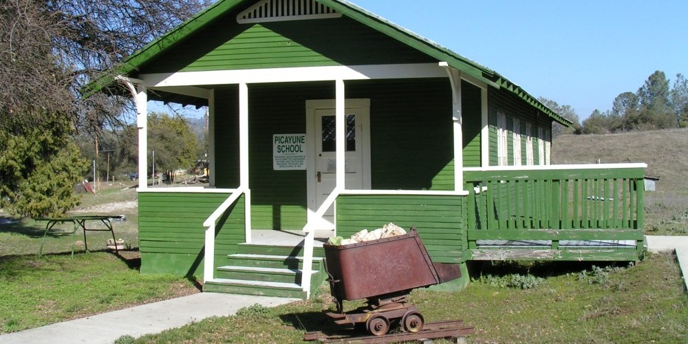 Picayune School for Chukchansi Indian children, 1913 to 1956; restored 2008 on the museum grounds.  Ore cart from one of numerous gold mines in this area. – Jack Good