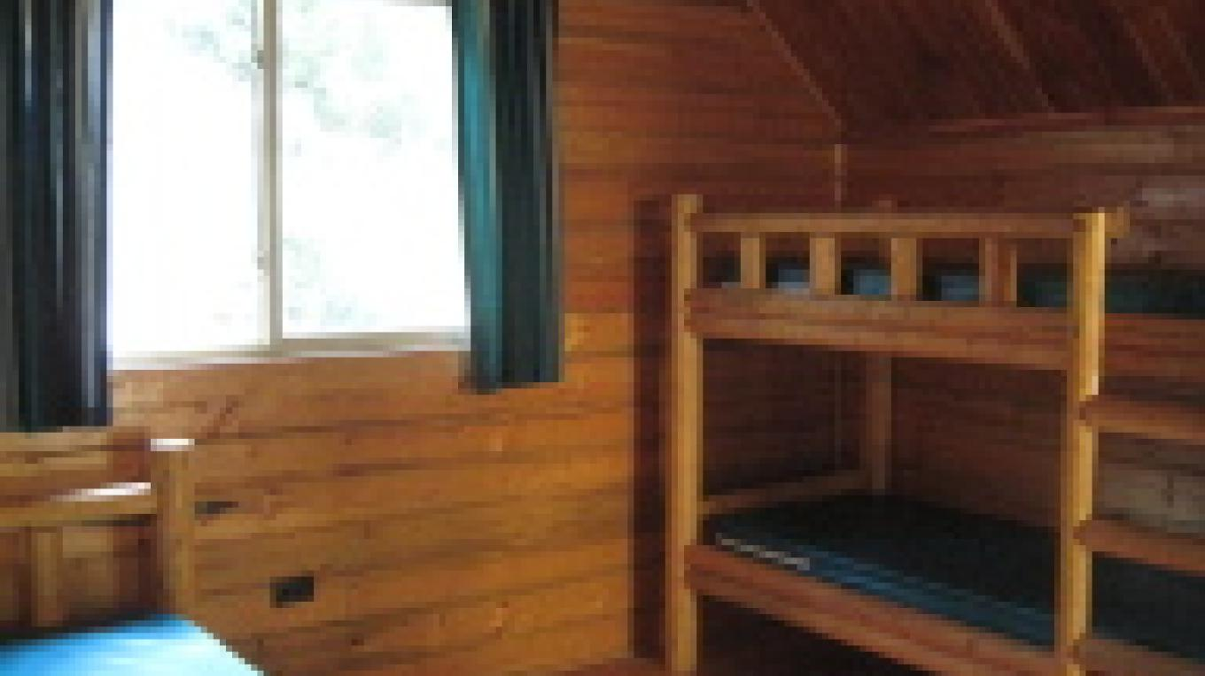 Inside a Log Camping Cabin with a double bed and separate bunk beds. – Zolldan Family